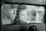 Casal acompanha pelo vidro molhado do carro